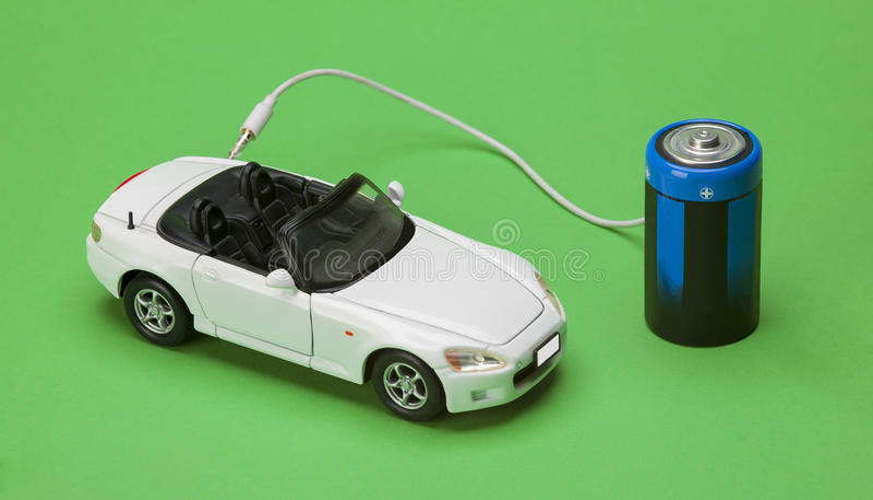 L'automobile di eco alimentata dalle batterie su fondo verde immagini stock