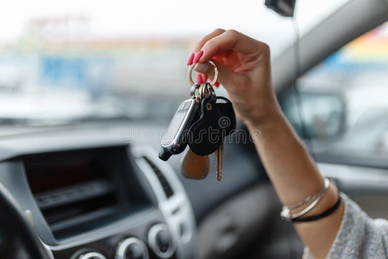 L'automobile digita la mano di una ragazza nell'interno dell'automobile Holdin della donna fotografia stock