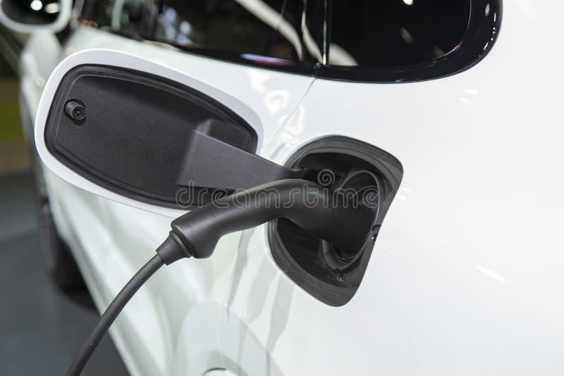 L'automobile elettrica alla stazione di carico con il rifornimento del cavo elettrico ha tappato Concetto ecologico dell'energia  fotografia stock