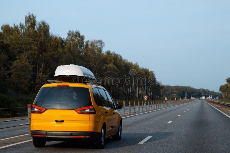 L'automobile gialla con le navi da carico del tetto sta guidando lungo l'estate fotografie stock libere da diritti