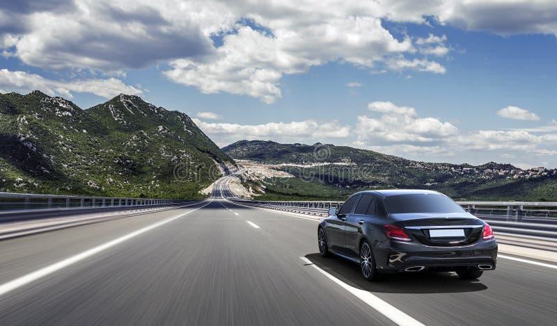 L'automobile guida velocemente su una strada principale negli altopiani immagine stock
