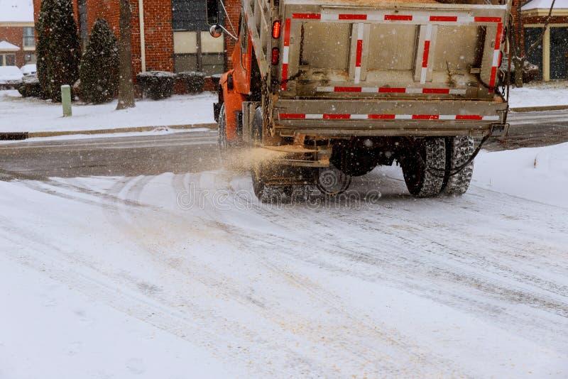 l'automobile municipale per spruzza la metà del sale e la sabbia sulle strade con neve fotografie stock