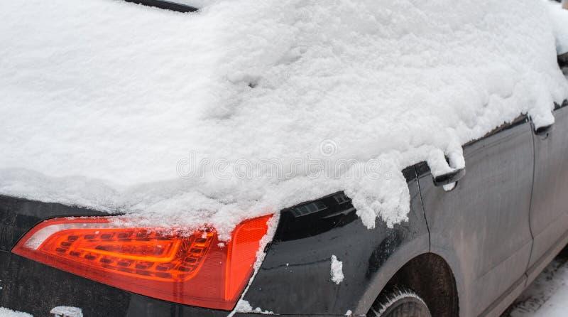 L'automobile nella neve, coperta di cumulo di neve bianco fotografia stock