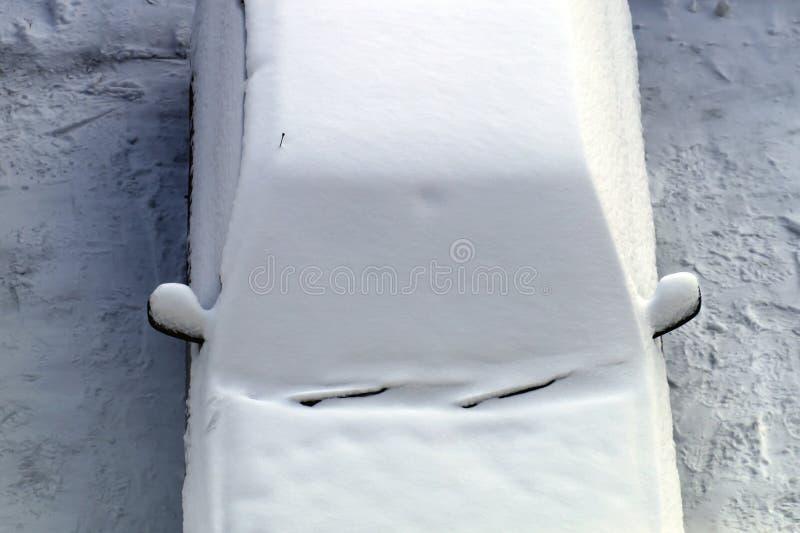 L'automobile parcheggiata è stata coperta di strato uguale di neve bianca fotografia stock