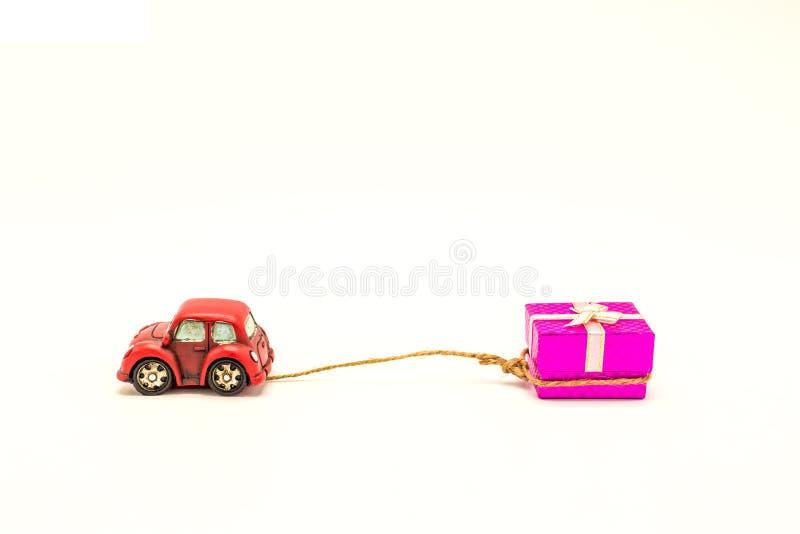 L'automobile rossa dello scarabeo sta trascinando il bianco rosa del contenitore di regalo immagini stock libere da diritti