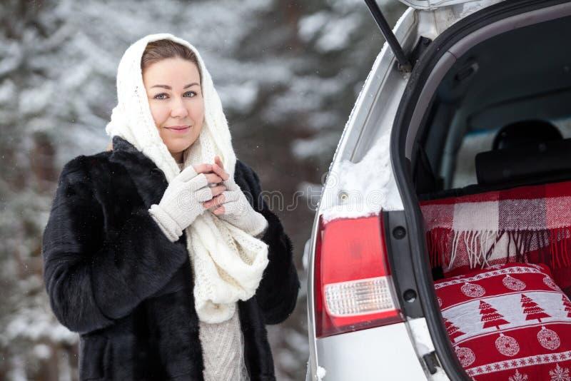L'automobile rotta con il tronco aperto in legno invernale, donna in vestiti caldi si congela con la bevanda calda in sue mani fotografia stock libera da diritti