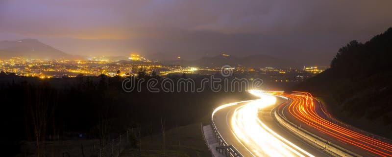 L'automobile si accende alla notte sulla strada che va alla città fotografie stock