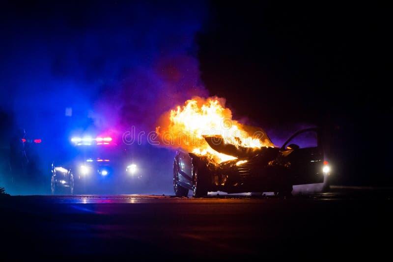 L'automobile su fuoco alla notte con la polizia si accende nel fondo fotografie stock