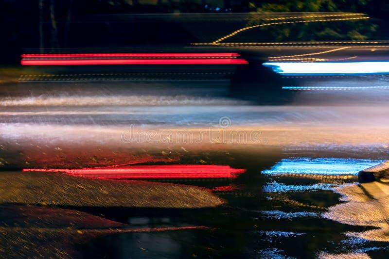 L'automobile vaga accende il fondo moto di velocità sulla via di notte fotografia stock