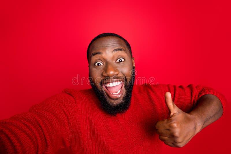 L'autoportrait de son joli joyeux joyeux et joyeux bonhomme à barbe content et joyeux, montrant des conseils de bosse photo libre de droits