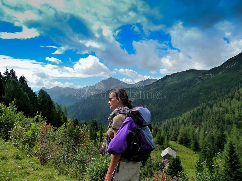 l'autriche Une fille sur une pente alpine de montagne le bleu opacifie le ciel pelucheux photos stock