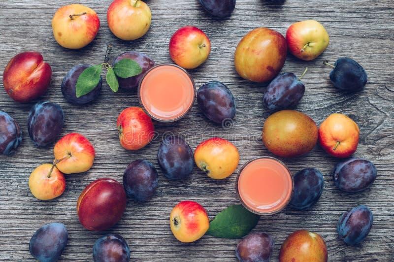 L'autunno fruttifica mele e prugna su un fondo di legno scuro, vista superiore Succo della prugna in piccoli vetri con frutta immagini stock