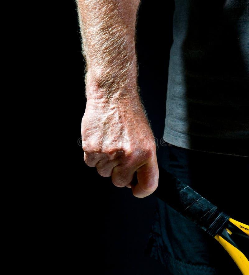 L'avant-bras de l'homme avec la raquette de tennis photographie stock