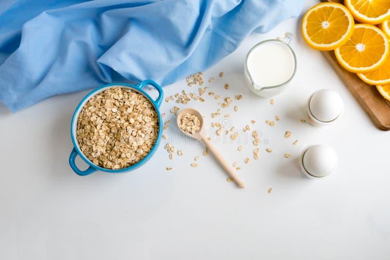 L'avena si sfalda piatto con latte, arancia, uova su una tavola bianca di legno Il punto di vista superiore dell'avena sana si sf fotografia stock libera da diritti
