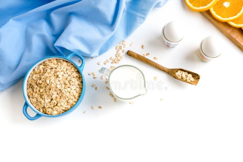 L'avena si sfalda piatto con latte, arancia, uova su una tavola bianca di legno Il punto di vista superiore dell'avena sana si sf immagine stock libera da diritti