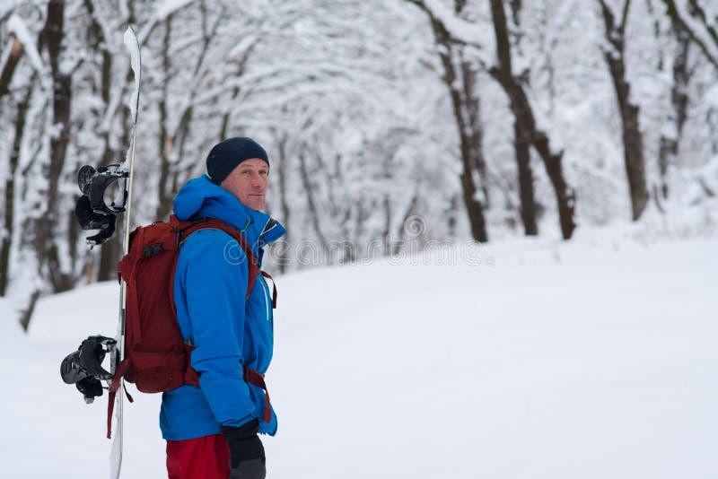 L'aventurier avec le surf des neiges et le sac à dos se tient dans la forêt images stock