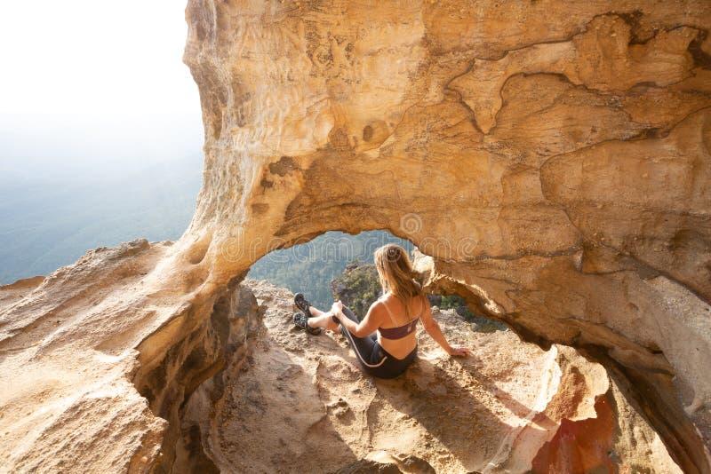 L'aventurier féminin rentre la falaise la caverne que supérieure regarde les montagnes bleues photographie stock