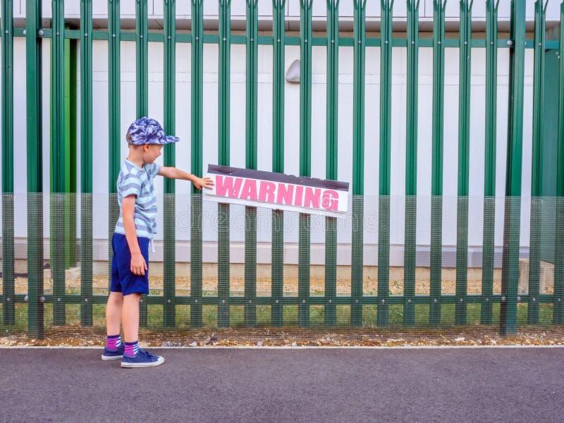 L'avertissement émouvant de garçon de petit enfant de vue de jour se connectent la barrière verte en métal au R-U image stock