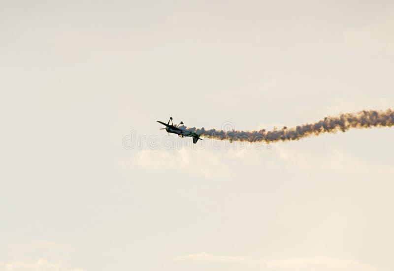 L'avion avec le vol coloré de fumée de trace dans le bleu opacifie les rayons acrobatiques aériens de ciel, d'exposition de casca photos libres de droits