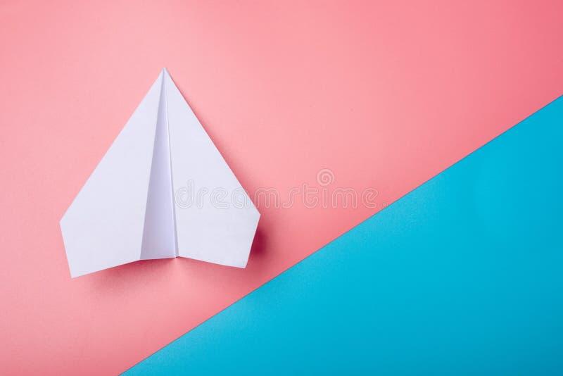 L'avion d'origami de livre blanc se trouve sur le fond de couleurs en pastel image stock