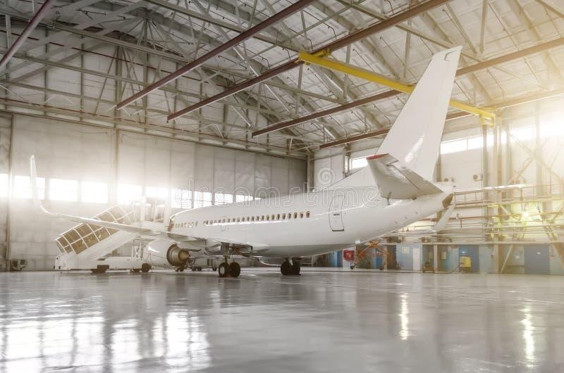 L'avion dans le hangar, derrière l'avion entier et la passerelle images libres de droits
