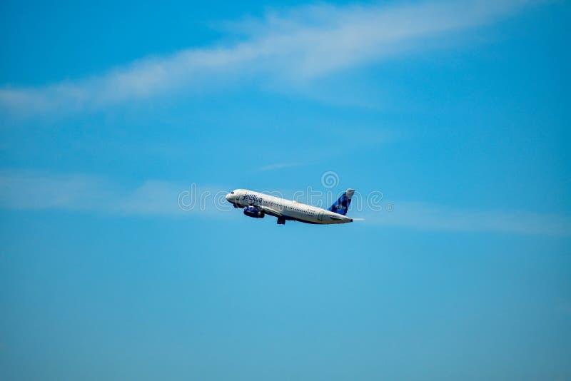 L'avion de Ba de Jetblue s'élève d'Orlando International Airport MCO sur le fond bleu-clair de ciel nuageux chez Orlando Internat photos stock