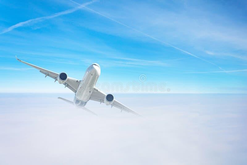 L'avion de passagers gagne en altitude en survolant une couche dense de nuages photos libres de droits
