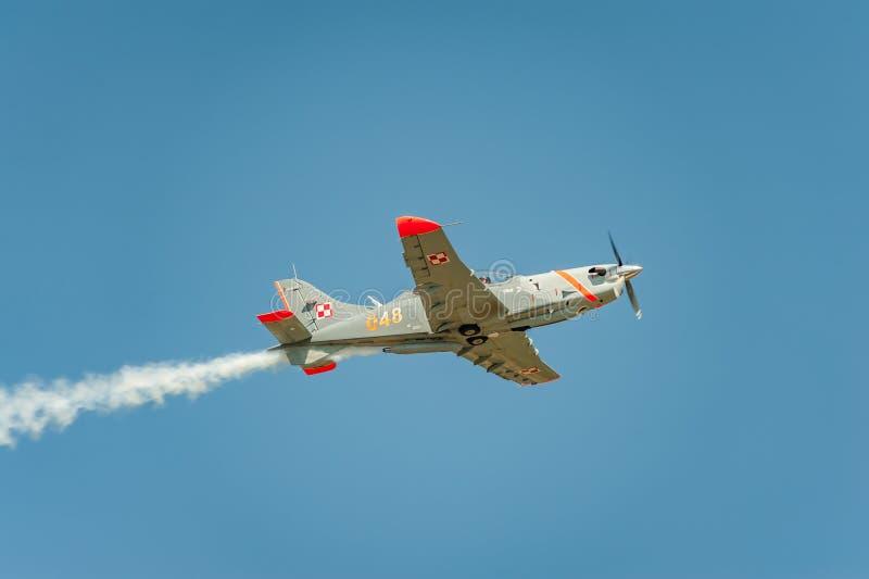 L'avion exécutant à l'airshow et aux feuilles derrière a fume dans le ciel photos libres de droits