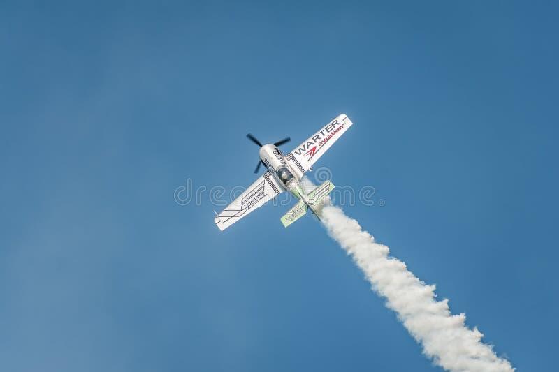 L'avion exécutant à l'airshow et aux feuilles derrière a fume dans le ciel image libre de droits