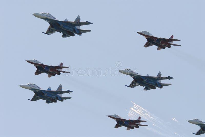 L'avion militaire MIG 29 et le SU 27 exécute le vol commun à un salon de l'aéronautique à Pushkin Russie 2007 photo stock