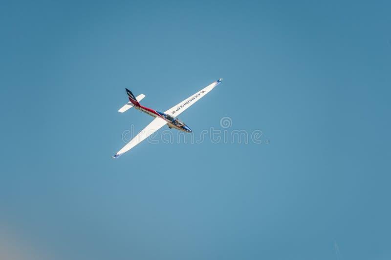 L'avion vole et montre une représentation au ciel bleu d'airshow en clair image stock