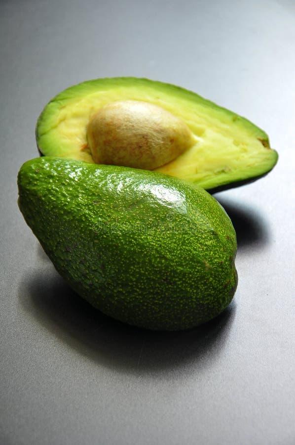 L'avocado verde divide in due le bugie su un fondo scuro fotografia stock