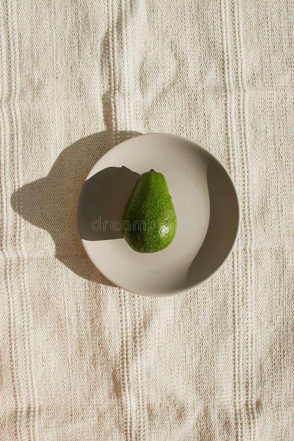 L'avocat mûr entier vert se trouve d'un plat en céramique gris au soleil Un avocat est sur un tapis naturel beige dans une lumièr image libre de droits