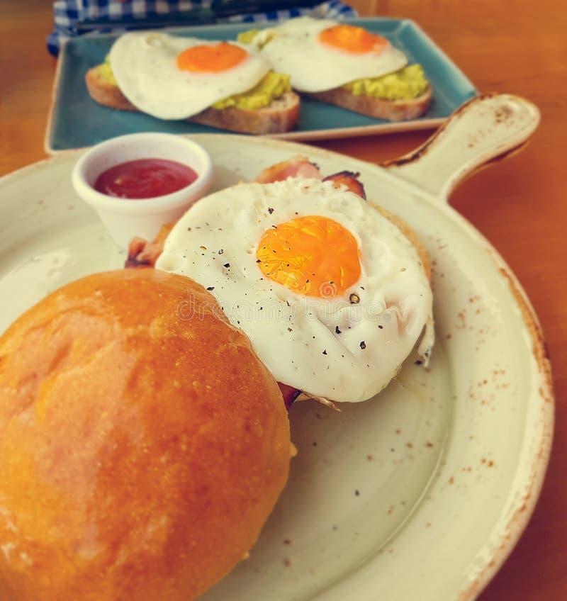 L'avocat organique de petit déjeuner d'alimentation saine grille avec le foyer sélectif de pain grillé d'oeufs au plat et de lard photographie stock libre de droits