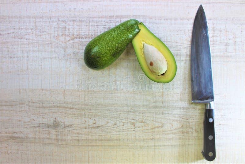L'avocat vert frais a coupé dans la moitié avec le couteau de chef sur une table en bois blanche comme fond dans la cuisine image stock