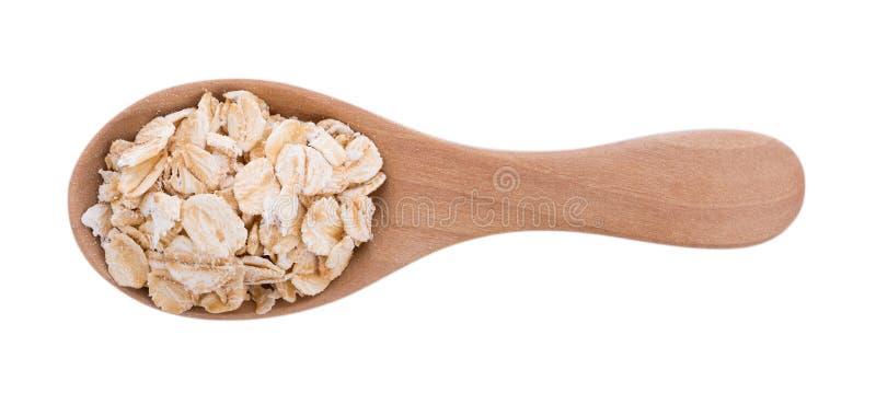 L'avoine s'écaille pile dans la cuillère en bois sur le fond blanc photo stock