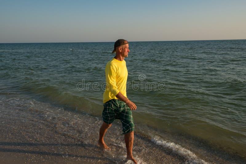 L'avventuriere allegro sta camminando seguendo la linea della spuma durante il tramonto fotografia stock libera da diritti