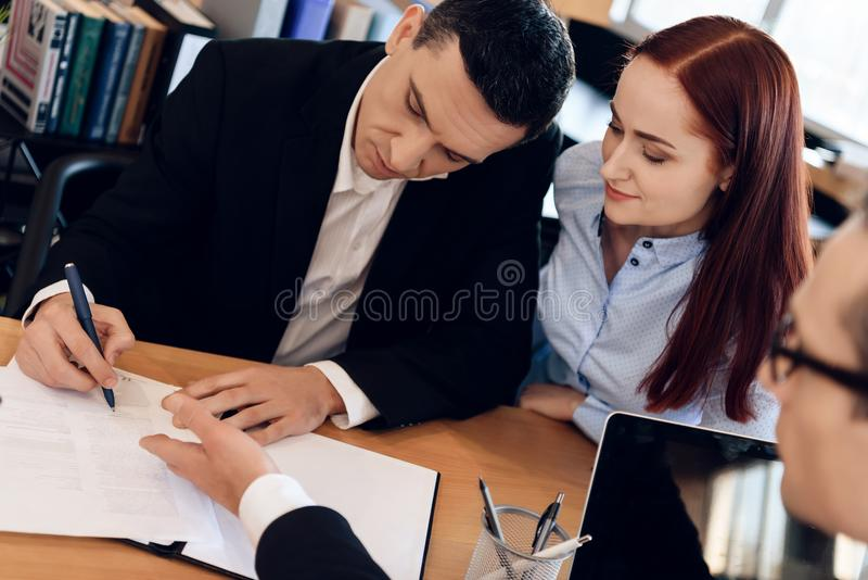 L'avvocato di divorzio mostra ad uomo dove firmare l'accordo della dissoluzione del matrimonio fotografie stock libere da diritti