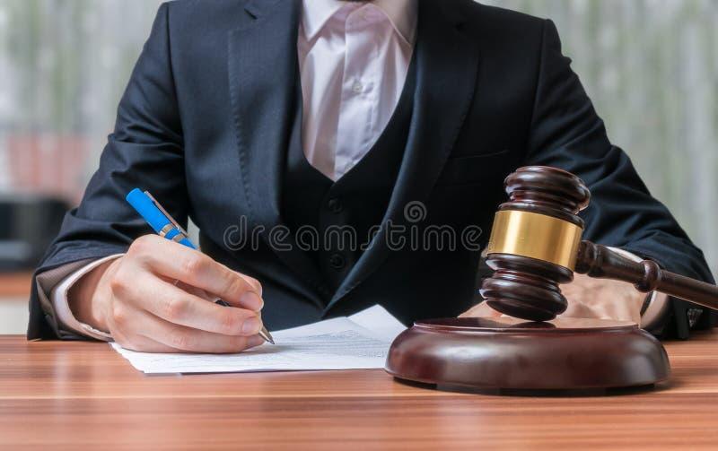 L'avvocato sta scrivendo e martelletto nella parte anteriore Giustizia e concetto di legge immagine stock libera da diritti