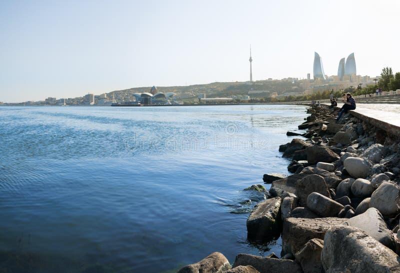 L'Azerbaigian, Bacu con i grattacieli delle torri della fiamma, la torre della televisione e la spiaggia del mar Caspio la gente  immagini stock libere da diritti