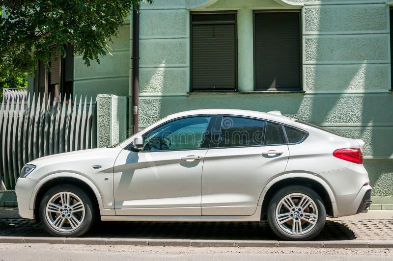 L'azionamento bianco della classe X di BMW X4 m. ha parcheggiato sulla via fotografia stock