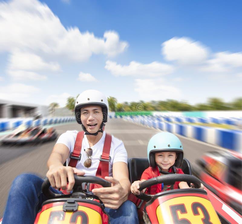 L'azionamento della figlia e del padre va kart sulla pista fotografia stock libera da diritti