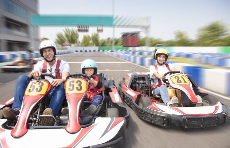 L'azionamento felice della famiglia va kart sulla pista immagine stock