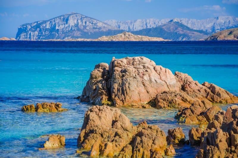 L'azur étonnant clair a coloré l'eau de mer sur la plage de Capriccioli avec des roches de granit, Sardaigne, Italie image stock