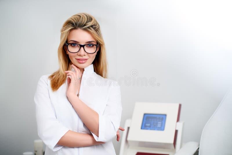L?chelnde ?berzeugte ?rztin mit Laborkittel auf in ihrem B?ro an stehen mit medizinischer Hardware und geduldigem Stuhl lizenzfreie stockfotos