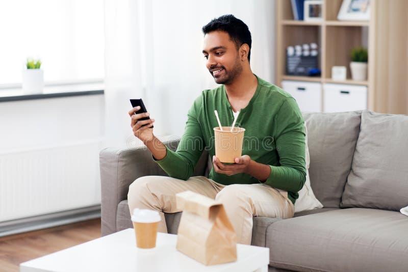 L?chelnde indische Fleisch fressende Mitnehmernahrung zu Hause lizenzfreie stockbilder