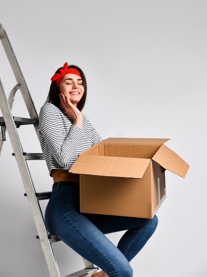L?chelnde junge Frau, die Pappschachtel auf wei?em Hintergrund h?lt stockfotografie