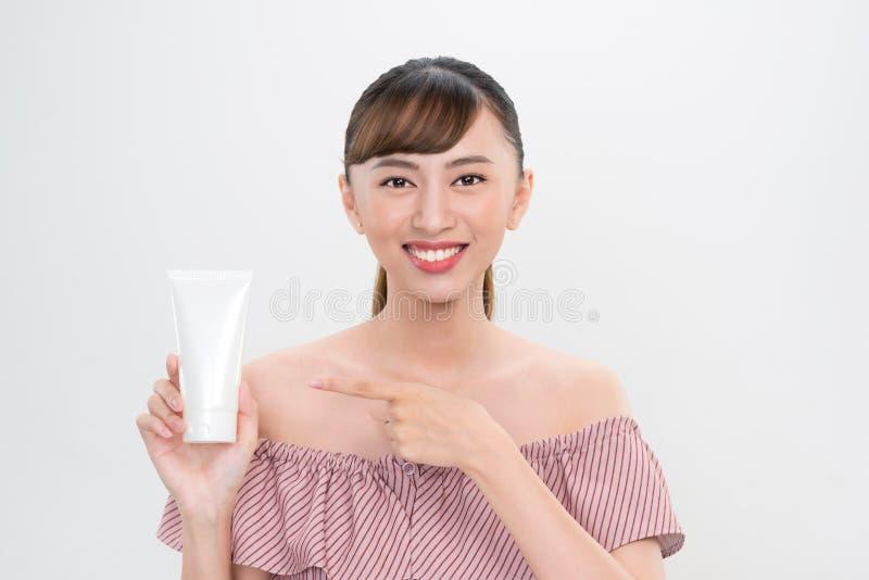 L?chelnde junge Frau, die skincare Produkte zeigt stockbild