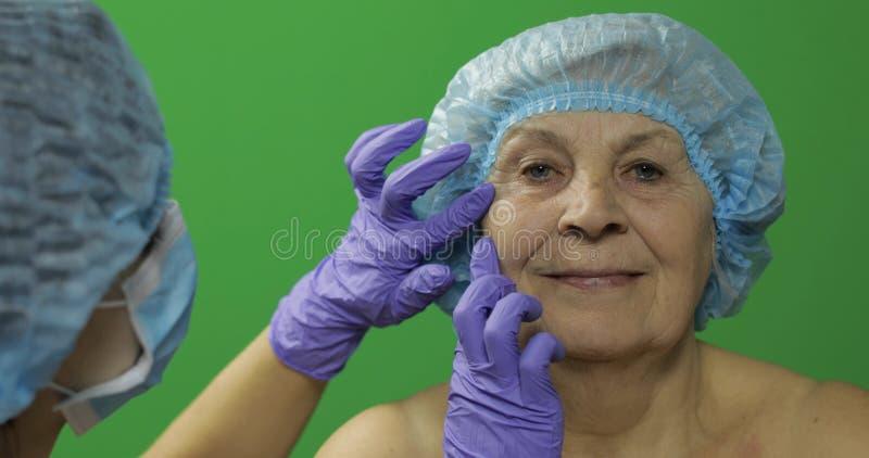 L?chelnde ?ltere Frau im sch?tzenden Hut Plastischer Chirurg, der Frauengesicht ?berpr?ft stockfotografie