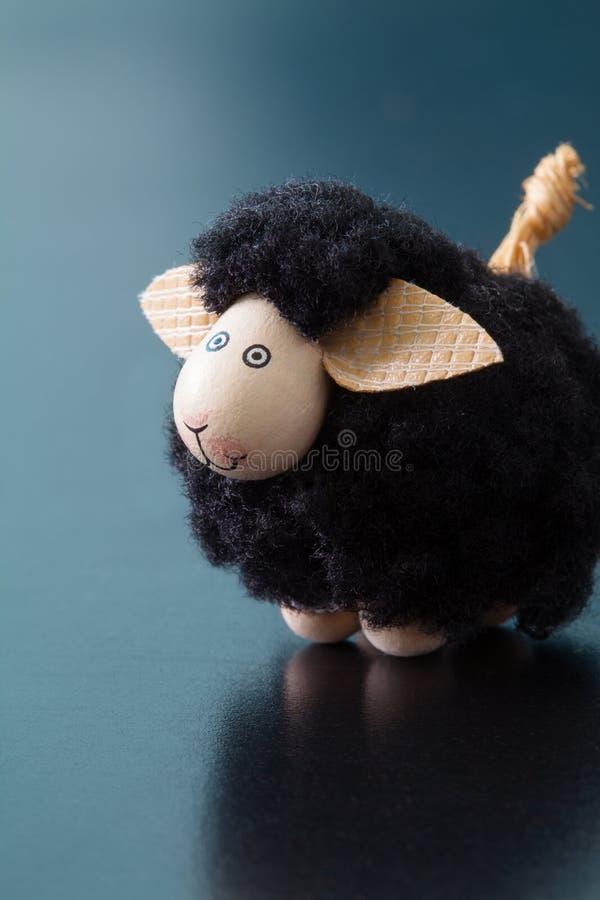 L?chelnde Spielzeugfig?rchen der schwarzen Schafe mit den gro?en Ohren auf einer blauen Oberfl?che lizenzfreie stockbilder
